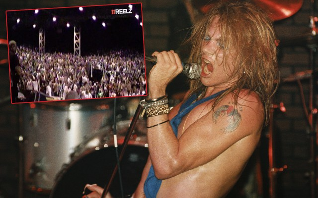 Axl Rose grips a microphone while wearing no shirt and sporting a blue scarf.