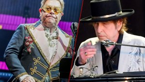 Elton John Wearing Yellow and Silver Glasses With Floral Embroided Blue Military Inspired Jacket at Piano, Bob Dylan Wearing Black Hat and Country Inspired Embroided Gray Blazer At Microphone
